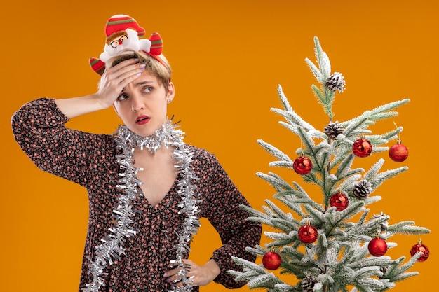 Bedauern junges hübsches mädchen mit weihnachtsmann-stirnband und lametta-girlande um den hals, das in der nähe des geschmückten weihnachtsbaums steht und die hand auf der stirn und auf der taille hält und die seite isoliert auf der orangefarbenen wand betrachtet