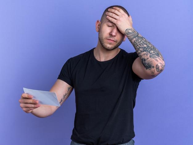 Bedauernd mit geschlossenen augen junger gutaussehender kerl, der ein schwarzes t-shirt trägt und ein ticket hält, das die hand auf die stirn legt, isoliert auf blauem hintergrund