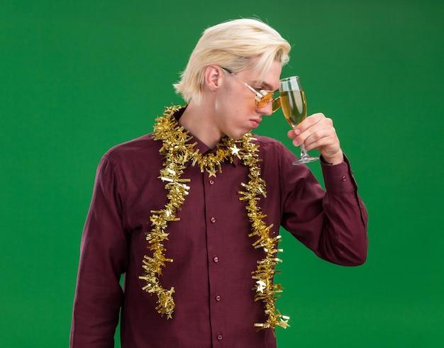 Bedauernder junger blonder mann, der eine brille mit lametta-girlande um den hals trägt, der kopf mit glas champagner berührt, der lokalisiert auf grünem hintergrund schaut