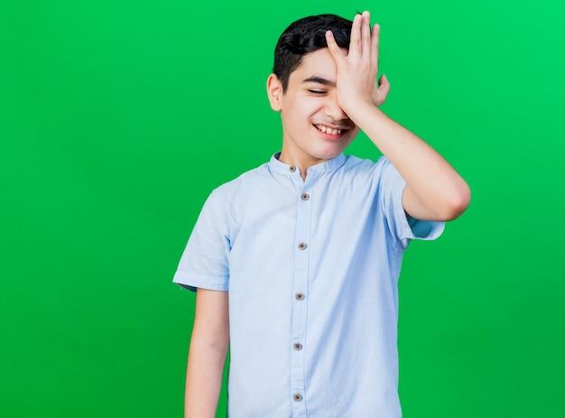Bedauernder junger kaukasischer junge, der hand auf stirn lokalisiert auf grünem hintergrund mit kopienraum setzt