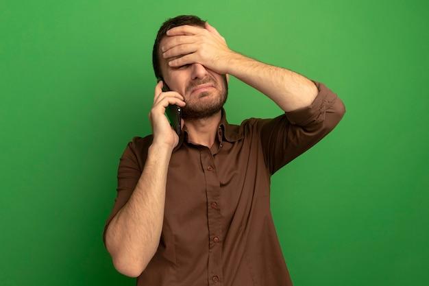 Bedauernder junger kaukasischer mann, der am telefon spricht und hand auf stirn mit geschlossenen augen lokalisiert auf grüner wand mit kopienraum setzt
