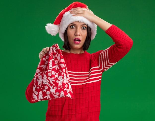 Bedauerndes junges mädchen, das weihnachtsmütze hält weihnachtsgeschenksack betrachtet kamera betrachtet hand auf kopf lokalisiert auf grünem hintergrund