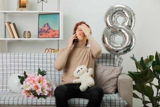 Bedauert bedecktes gesicht mit handlichem gutaussehendem kerl am glücklichen frauentag, der teddybären hält, spricht am telefon, das auf sofa im wohnzimmer sitzt