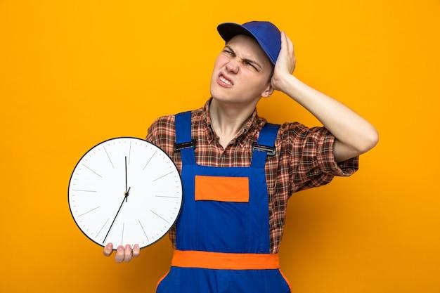 Bedauert, die hand auf den kopf zu legen, junger reinigungsmann, der uniform und mütze trägt, die eine wanduhr hält