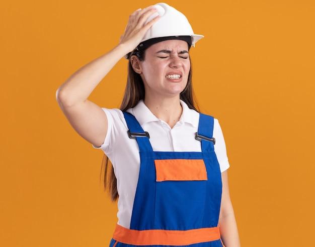 Bedauert mit geschlossenen augen junge baumeisterin in uniform isoliert auf orange wand