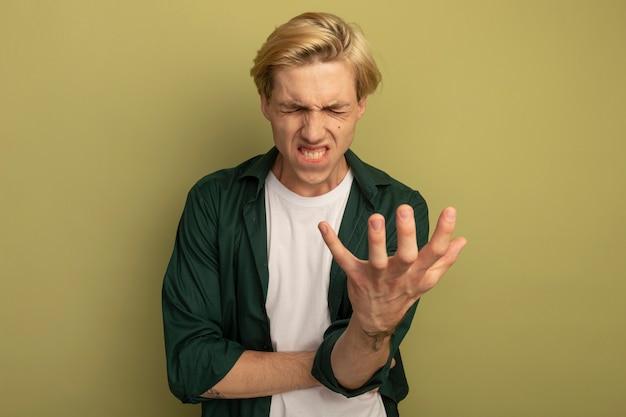 Bedauert mit geschlossenen augen junger blonder kerl, der grünes t-shirt trägt, das hand aushält