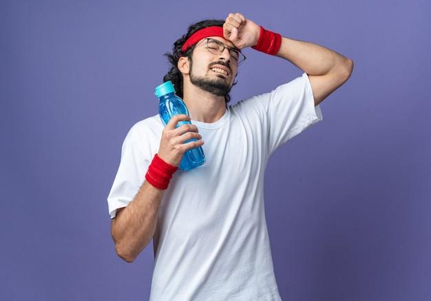 Bedauert mit geschlossenen augen junger sportlicher mann mit stirnband mit armband, das eine wasserflasche hält und die hand auf die stirn legt