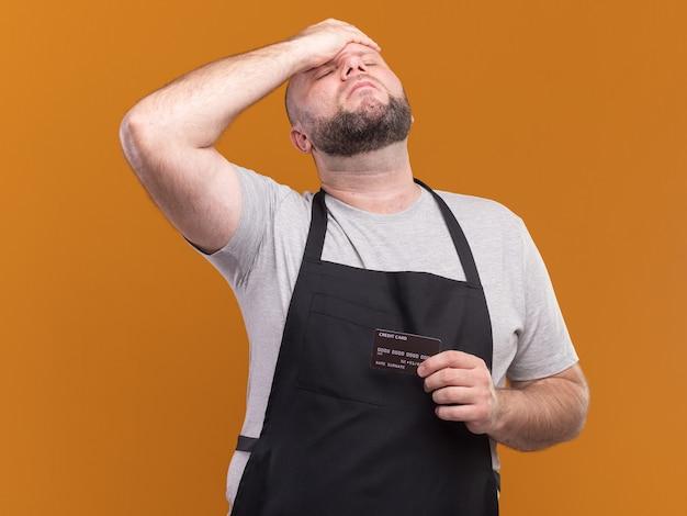 Bedauert mit geschlossenen augen slawischen männlichen friseur mittleren alters in uniform, die kreditkarte hält und hand auf stirn lokalisiert auf orange wand legt