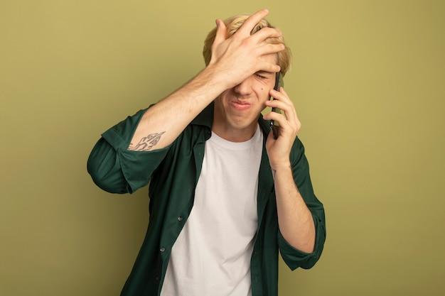 Bedauerter junger blonder kerl, der grünes t-shirt trägt, spricht am telefon und legt hand auf stirn