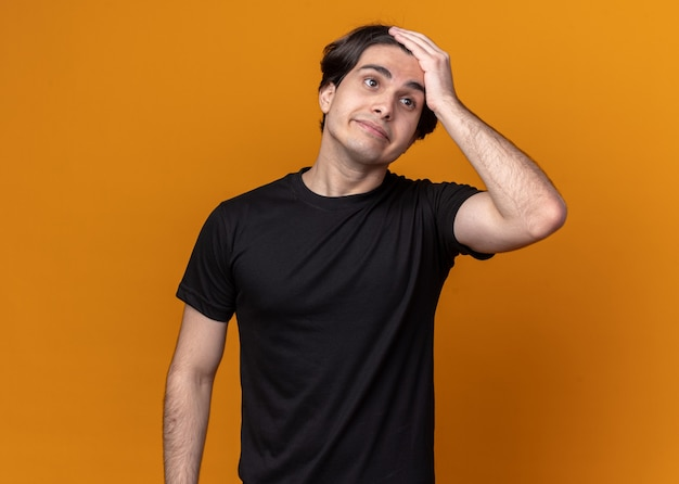 Bedauerter junger gutaussehender kerl mit schwarzem t-shirt, der hand auf die stirn legt, isoliert auf oranger wand?