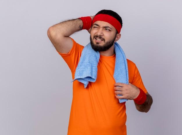 Bedauerter junger sportlicher mann, der seite betrachtet, die stirnband und armband mit handtuch auf schulter trägt, die hand auf kopf lokalisiert auf weißem hintergrund setzt