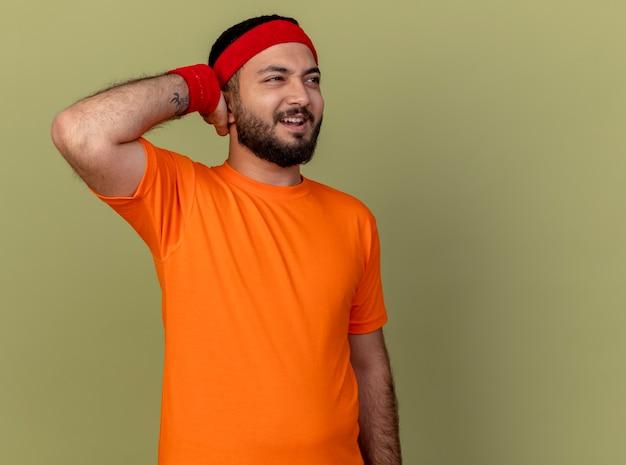 Bedauerter junger sportlicher mann, der seite betrachtet, die stirnband und armband setzt, die hand setzen
