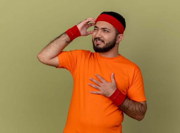 Bedauerter junger sportlicher mann, der seite betrachtet, die stirnband und armband trägt und hände auf brust und schläfe lokalisiert auf olivgrünem hintergrund setzt