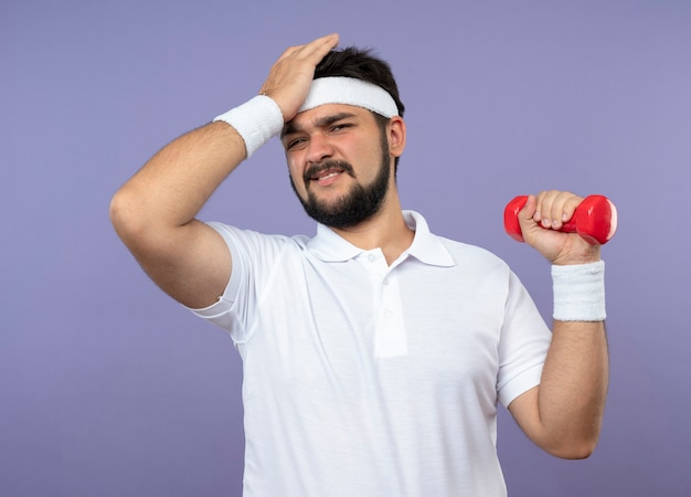 Bedauerter junger sportlicher mann, der stirnband und armband hält hantel hält hand auf stirn legt