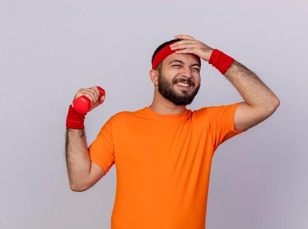 Bedauerter junger sportlicher mann, der stirnband und armband trägt, die hantel setzen hand