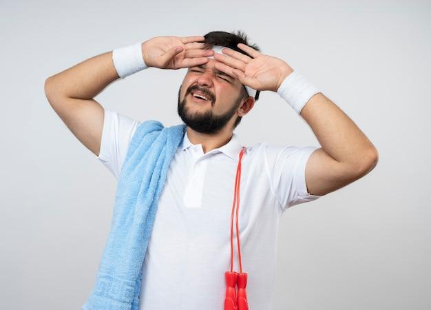 Bedauerter junger sportlicher mann mit geschlossenen augen, der stirnband und armband mit handtuch und springseil auf schulter trägt und hände auf stirn lokalisiert auf weißer wand setzt