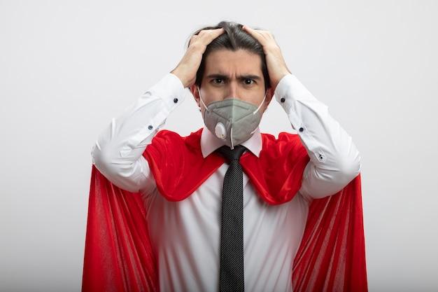 Bedauerter junger superheld, der kamera betrachtet, die krawatte und medizinische maske trägt, packte den kopf lokalisiert auf weißem hintergrund