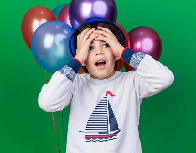 Bedauerter kleiner junge mit blauem partyhut, der vor ballons stand, packte den kopf