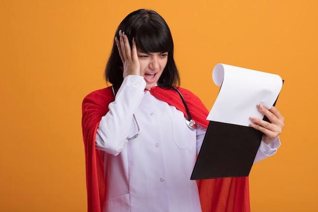Bedauertes junges superheldenmädchen, das stethoskop mit medizinischem gewand und umhang trägt, das durch zwischenablage flippt und hand auf kopf lokalisiert auf orange wand setzt