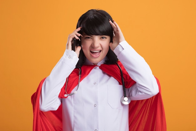 Bedauertes junges superheldenmädchen, das stethoskop mit medizinischer robe und umhang trägt telefon hält und kopf packt