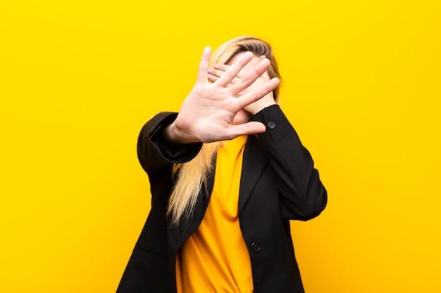Bedecken sie das gesicht mit der hand und legen sie die andere hand nach vorne, um die kamera anzuhalten und fotos oder bilder abzulehnen