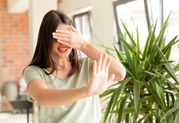 Bedecken sie das gesicht mit der hand und legen sie die andere hand nach vorne, um zu verhindern, dass die kamera fotos oder bilder ablehnt