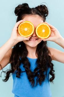 Bedeckungsaugen des kleinen mädchens mit orange scheiben
