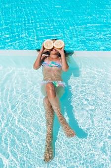 Bedeckungsaugen des kleinen mädchens mit zitronenhälften nähern sich augen auf swimmingpool