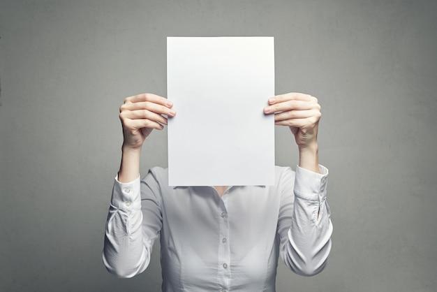 Bedeckungsgesicht der anonymen frau mit papierblatt