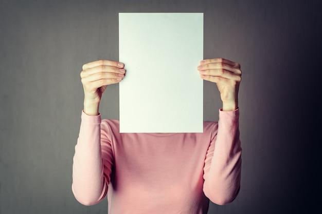 Bedeckungsgesicht der anonymen frau mit weißbuchblatt