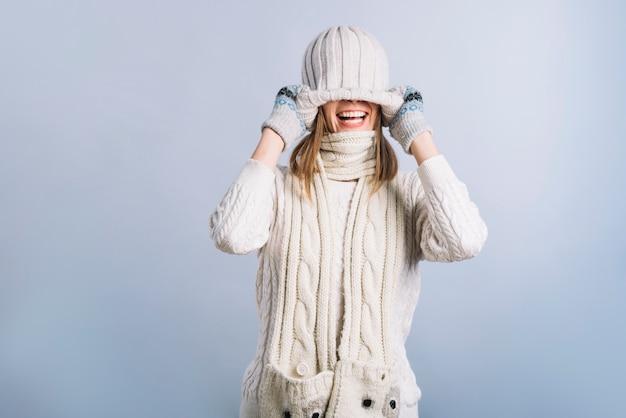 Bedeckungsgesicht der jungen frau mit kappe