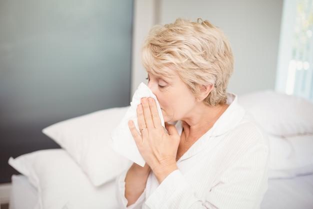 Bedeckungsnase der älteren frau beim zu hause niesen