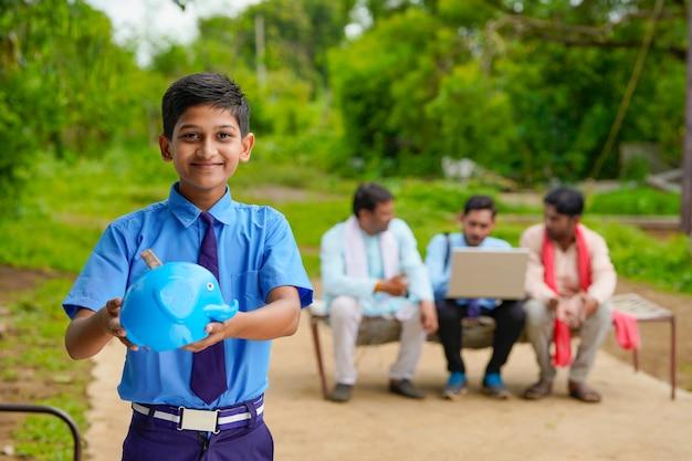 Bedeutung des sparkonzepts: intelligenter indischer kleiner junge, der zu hause das sparschwein in der hand steht und hält.