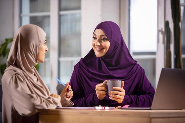 Bedeutungen. glückliche und junge zwei muslimische frauen zu hause während des unterrichts, studieren in der nähe von computer, online-bildung. kultur, traditionen, moderne menschen. am pc-monitor gucken, einkaufen oder reden.