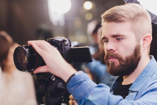 Bediener bei der arbeit mit einer großen professionellen kamera. videographer dreht clip für berühmten star.