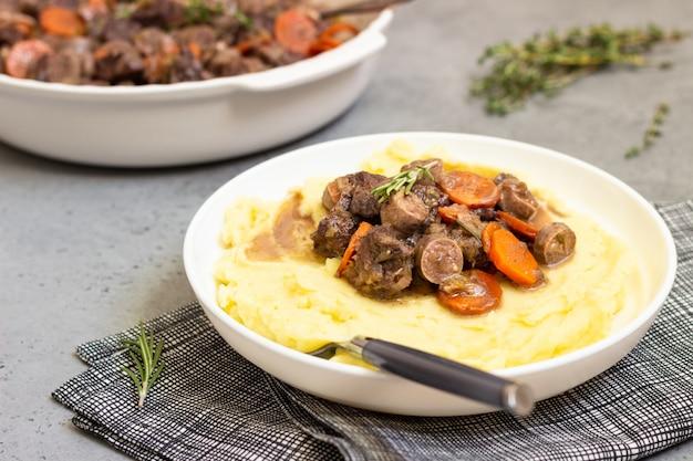 Beef bourguignon oder fleischeintopf mit gemüse und kräutern.