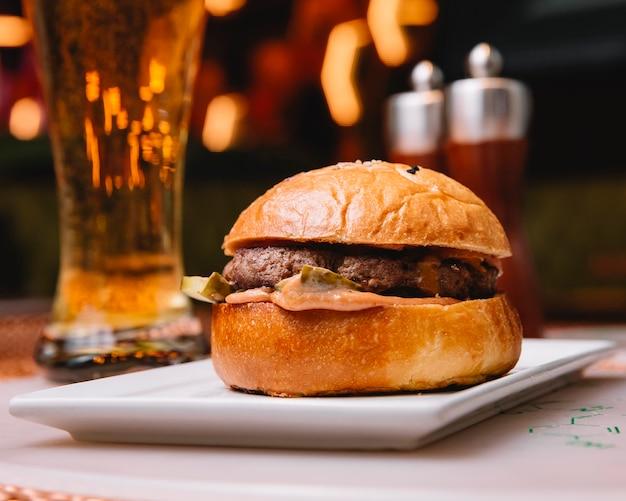 Beef burger mit sauce eingelegte gurke serviert im restaurant mit bier