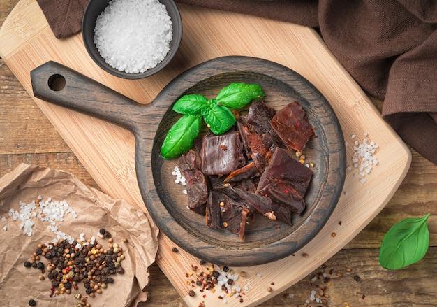 Beef jerky mit salz, pfeffer und basilikum auf einem holzteller an einer hellen wand. ansicht von oben. natürliche, gesunde snacks.