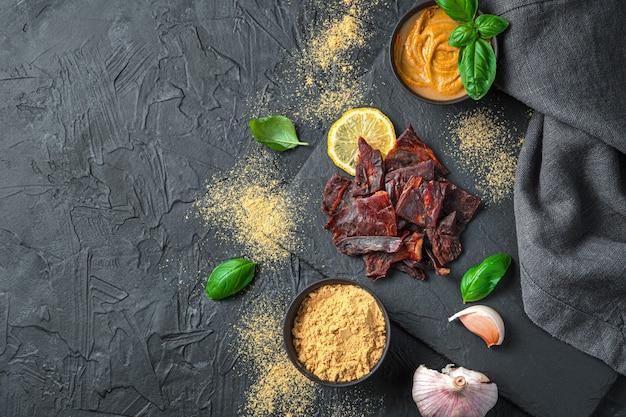 Beef jerky mit senf, knoblauch und basilikum an einer schwarzen wand. ansicht von oben, kopienraum.