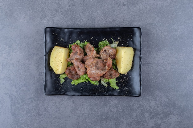 Beef kebab und salzkartoffeln auf schwarzem teller.