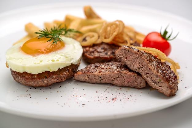 Beef rissole, saftiges steak-rindfleisch mit tomaten und kartoffeln