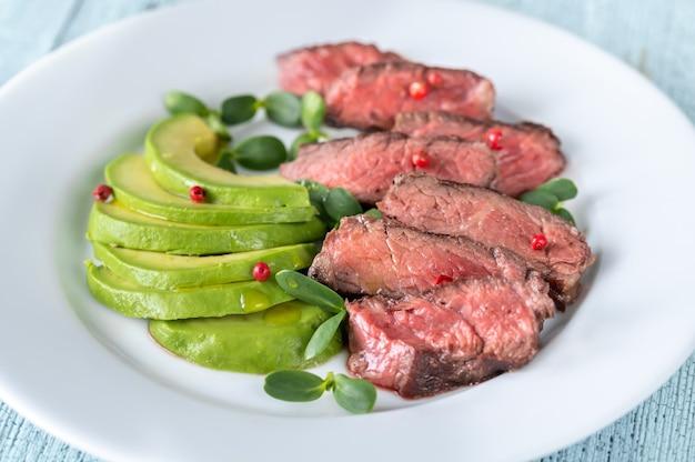 Beefsteak mit rotem pfefferkorn dekoriert und mit avocado-scheiben garniert