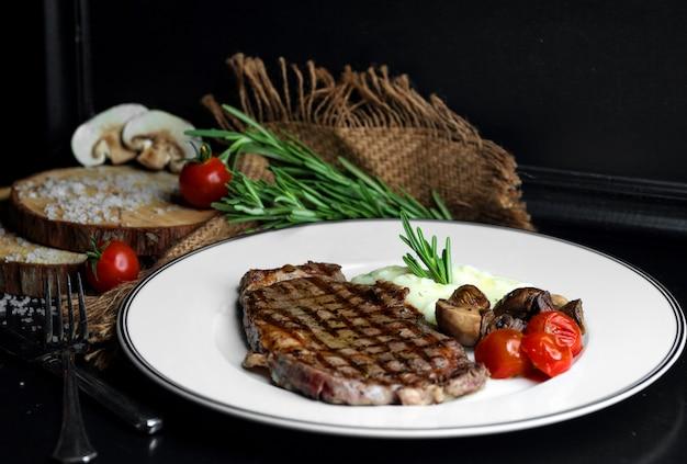 Beefsteak serviert mit reis, champignons und tomaten
