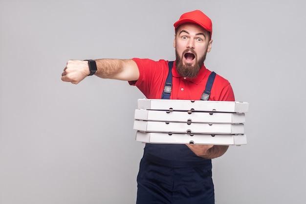 Beeil dich! zeit ist vergangen. junger erstaunter lieferbote mit bart in blauer uniform und rotem t-shirt, der einen stapel pizzakartons aus pappe auf grauem hintergrund hält. innen, studioaufnahme, isoliert, kopienraum.