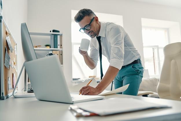 Beeilen, um dinge zu erledigen. hübscher junger mann in hemd und krawatte, der etwas schreibt und lächelt, während er im büro steht