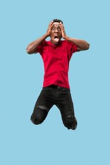 Beeindruckend. attraktives männliches porträt auf blauem studiohintergrund. junger emotionaler überraschter afromann, der mit offenem mund springt. menschliche emotionen, gesichtsausdruckkonzept. trendige farben