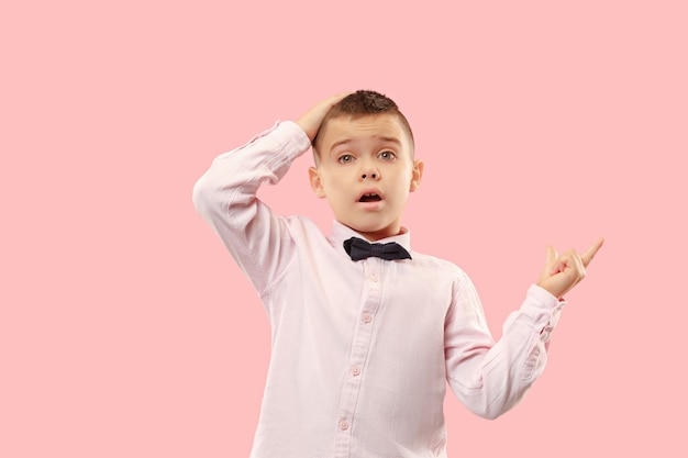 Beeindruckend. attraktives männliches porträt in halber länge auf rosa studio-hintergrund. junger emotional überraschter jugendlich junge, der mit offenem mund steht. menschliche emotionen, gesichtsausdruckkonzept. trendige farben