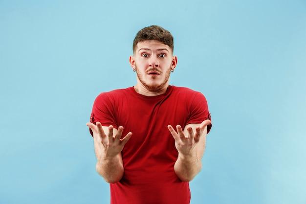 Beeindruckend. attraktives männliches vorderporträt in halber länge auf blauem studiohintergrund. junger emotionaler überraschter bärtiger mann, der mit offenem mund steht. menschliche emotionen, gesichtsausdruckkonzept. trendige farben