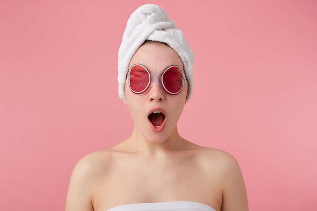 Beeindruckend! coole neuigkeiten! junges glückliches erstauntes mädchen nach dem spa mit einem handtuch auf dem kopf und einer maske auf den augen, mit weit geöffnetem mund und augen, hört coole nachrichten, steht auf.