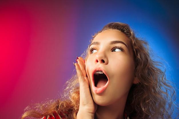 Beeindruckend. schönes weibliches halblanges vorderes porträt auf rotem und blauem studiohintergrund. junge emotionale überraschte frau, die mit offenem mund steht. menschliche emotionen, gesichtsausdruckkonzept.